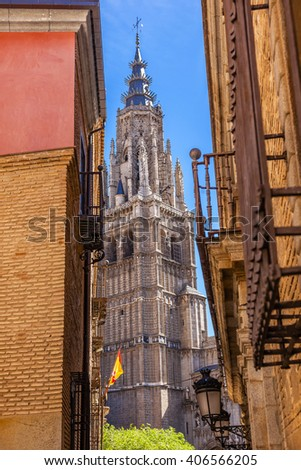 Cathedral Spire Tower Spanish Flag Narrow Streets Medieval City Toledo Spain.  Cathedral started in 1226 finished 1493 - stock photo