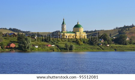 cathedral with bell tower in russian village on river bank