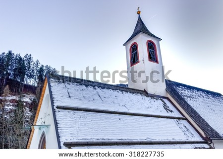 Catholic cemetery with church on high mountains overlooking snowy peaks and pine forest - stock photo