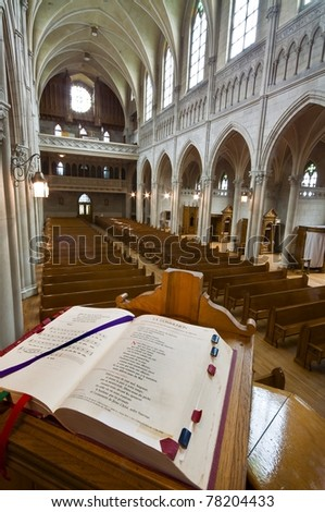 Catholic church interior, from the pulpit. Open Bible in foreground. - stock photo