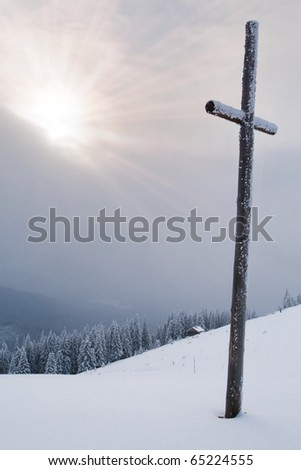 catholic cross in the mountains in winter - stock photo