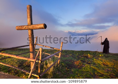 Catholic cross on a mountaintop and death that stands apart - stock photo