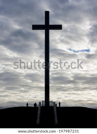Catholic cross silhouette against the cloudy sky - stock photo