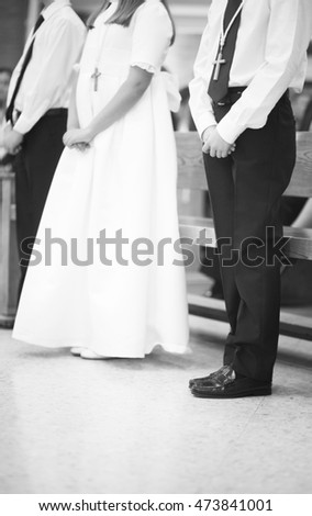 Catholic first communion religious ceremony girl in white dress and boys in church.