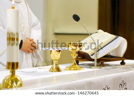Catholic Mass - holly sacrifice of blood and body of Jesus Christ in landscape orientation photo, focused to hands of priest - stock photo