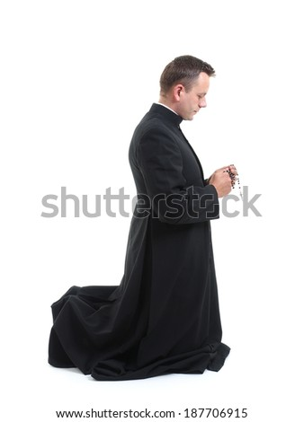 Catholic priest klneeling and saying his rosary beads  - stock photo