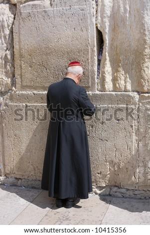 Catholic priest prays in the western wall in Jerusalem. - stock photo
