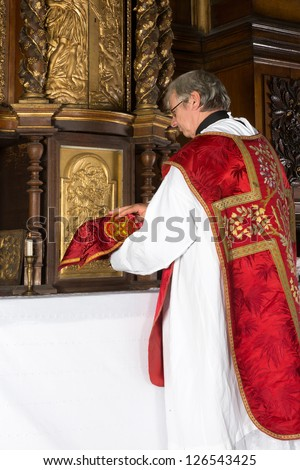 Catholic priest putting a covered chalice back into the tabernacle of a medieval church with 17th century interior - stock photo