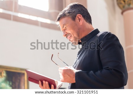 Catholic priest reading bible in church - stock photo