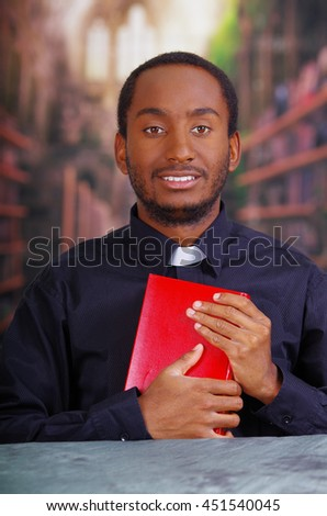 Catholic priest wearing traditional clerical collar shirt sitting and holding bible looking into camera, religion concept - stock photo