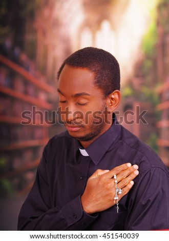 Catholic priest wearing traditional clerical collar shirt standing performing sign of the cross and holding rosary in hand, religion concept - stock photo