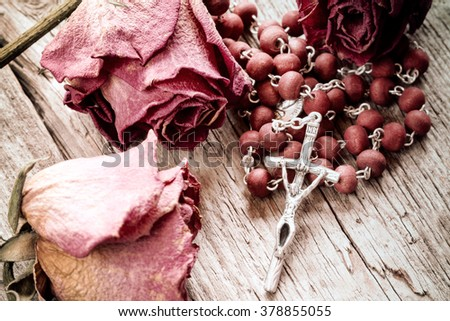 Catholic rosary and faded roses on old wooden background - stock photo