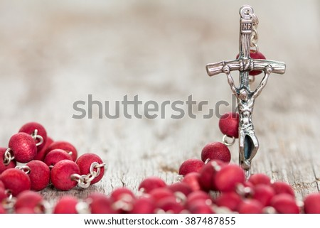 Catholic rosary on old wooden  background. Selective focus. - stock photo