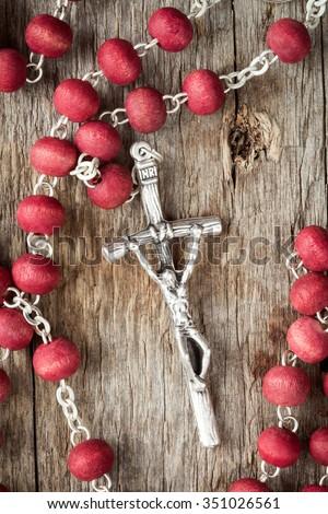 Catholic rosary on old wooden texture background - stock photo