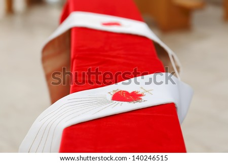 Catholic stole in catholic church, focused to the red heart with cross - stock photo