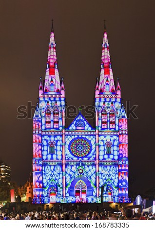 Catholic tall stone cathedral with 2 towers highlighted by light show at Christmas celebration after sunset as performing show for surrounding people - stock photo