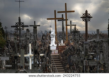 Catholicism religion landmark - The Hill of Crosses in Lithuania under heavy dark cloudy sky - stock photo