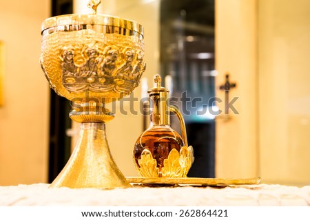 Catholics bread and wine in chalice with crucifix in background  - stock photo