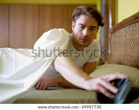 caucasian adult man in bed snoozing alarm clock and waking up. Horizontal shape, waist up, front view