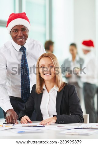Caucasian and African-american co-workers looking at camera on background of their colleagues - stock photo
