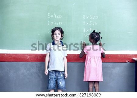 Caucasian and afroamerican schoolkids learning math on chalkboard. - stock photo