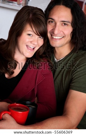 Caucasian and Native American couple snuggling at a cafe