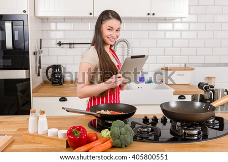 Caucasian attractive woman with tablet in the kitchen. - stock photo