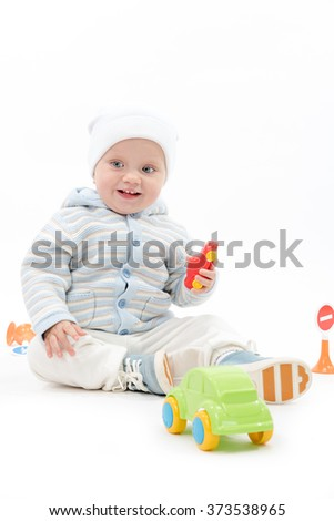 caucasian baby boy child playing with cars warm clothing hat sitting isolated on white studio shot - stock photo