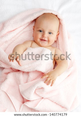 Caucasian baby boy covered with pink towel joyfully smiles at camera - stock photo