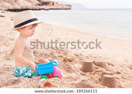 Caucasian baby (boy) is sitting at the beach. Happy child is playing with toys and shellfishes in summer day. Copy space. Close up, outdoor (Sharm El Sheikh, Egypt). - stock photo