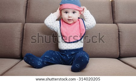 Caucasian baby boy with glasses sitting on brown sofa at home - stock photo