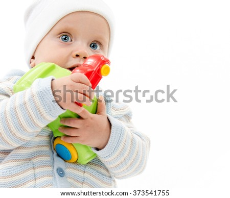 caucasian baby child boy 1 year playing with cars standing isolated on white studio shot warm clothing hat