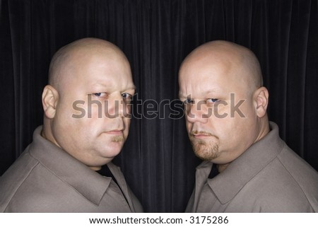 Caucasian bald mid adult identical twin men looking sternly at viewer. - stock photo