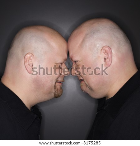 Caucasian bald mid adult identical twin men standing face to face with angry expression. - stock photo