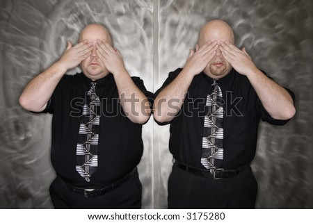 Caucasian bald mid adult identical twin men standing with hands covering eyes. - stock photo