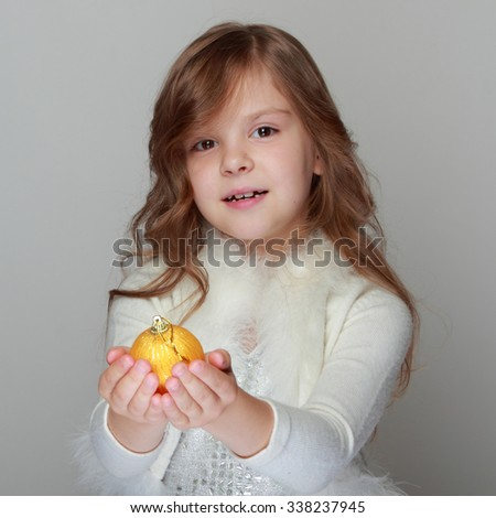 Caucasian beautiful little girl in a shiny dress with cute yellow hair holding a Christmas ball on a gray background/Christmas and New Year decoration - stock photo