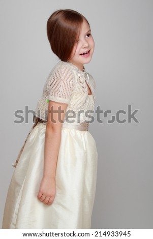 Caucasian beautiful little girl in dress with long hair on grey background