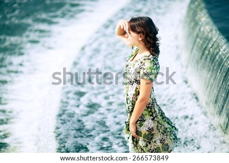 Caucasian beautiful teen girl with dark hair and blue eyes is standing in the flowing water near a waterfall. Looking at camera and smiling playing with her hair Her summer dress flying with the wind. - stock photo