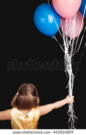 Caucasian blond little girl with colorful balloons, rear view over black background - stock photo