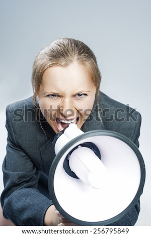Caucasian Blond Woman Shouting Using Megaphone. Against Grey Background. Vertical Image - stock photo