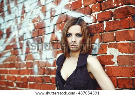 Caucasian blond woman standing behind brick wall