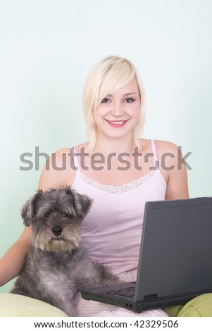 Caucasian blond young woman sitting on bed working on portable notebook pc computer together with dog of Schnauzer breed