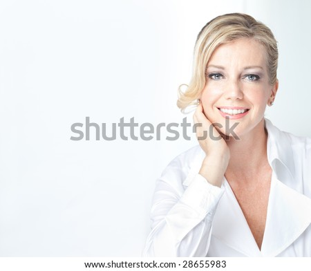 Caucasian blonde mature looking business woman in white smiles casually - stock photo