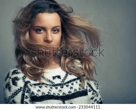 Caucasian blonde model with long wavy hair in the air and perfect light skin wearing jumper. Toned in warm colors, Cosmetics concept, Horizontal shot, studio - stock photo