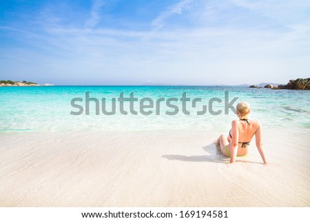 Caucasian blonde woman relaxing on the white  sandy beach enjoying the turquoise blue sea. - stock photo