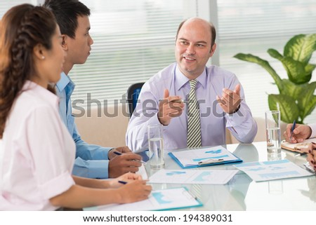 Caucasian boss having meeting with his young Veitamese colleagues - stock photo
