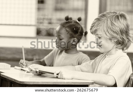 Caucasian boy and african girl doing work in elementary classroom. - stock photo