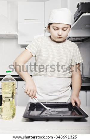 Caucasian boy covers pan with oil by brush while cooking at the kitchen to prevent dough sticking  - stock photo