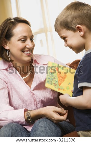 Caucasian boy giving mid adult mother a drawing. - stock photo