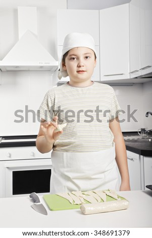 Caucasian boy holding raw croissant made by himself while standing at the kitchen - stock photo